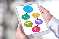 Business strategy improvement concept on a tablet. Man holding a tablet showing business strategy improvement concept Royalty Free Stock Images