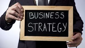 Business strategy written on blackboard, male in black suit holding sign, career Royalty Free Stock Photo