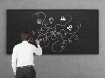 Business strategy. Young businessman drawing business strategy on wall Stock Image