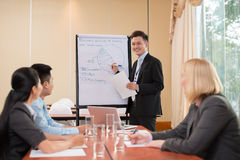 Business strategy. A young businessman explaining business strategy on the foreground Royalty Free Stock Image