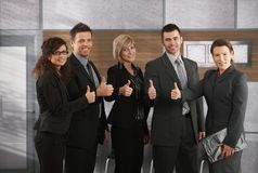 Business success. Portrait of happy successful business team showing thumbs up to camera in office Royalty Free Stock Images