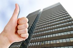 Business Success. A thumbs up and a tall business building.  Success in Business Royalty Free Stock Photos