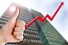 Business Success. A thumbs up with a graph line going up and up. A tall business building in the background with a lens flare. Success in Business Stock Images