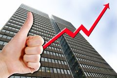 Business Success. A thumbs up with a graph line going up and up, with a tall business building in the background. Success in Business Royalty Free Stock Image