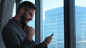 Business success and achievement - happy businessman cheering celebrating on cell phone. Young urban professional. Successful business man reaching personal stock video footage