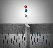 Business Success Agreement Concept. As two groups of people divided by a wall with business leaders using balloons to rise above the obstacle as a success Stock Images