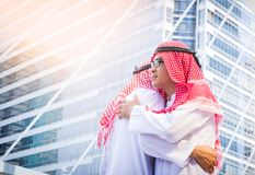 Business success concept. Asian muslim businessman   greeting wi. Th a hug on city background Royalty Free Stock Image