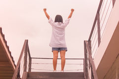 Business Success Concept : Asian woman standing on top of stair and raise up her hands. stock photography