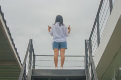 Business Success Concept. Business Success Concept : Asian woman standing on top of stair with raise up her hands and giving a thumbs up gesture Royalty Free Stock Photo
