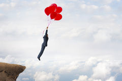 Business success concept. Businessman flying upward with helium balloons Stock Images