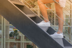 Business Success Concept : Woman is walking up black metal stairs outside the buildings. Royalty Free Stock Photography