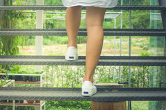 Business Success Concept : Woman is walking up steel stairs outside in the garden with green natural background. Autumn filter effect Royalty Free Stock Photos