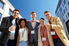 Business team with conference badges in city. Business, success and corporate concept - international group of people with name tags or conference badges showing Royalty Free Stock Images