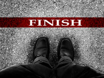 Business Success. Finish line with businessman wearing dress shoes as metaphor for finishing work as a winner Stock Image