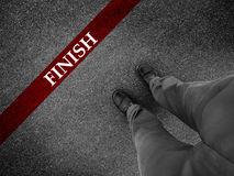 Business Success. Finish line with businessman wearing dress shoes as metaphor for finishing work as a winner Royalty Free Stock Photo