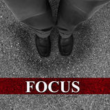 Business Success Through Focus. Businessman standing on asphalt starting line with motivation word of Focus royalty free stock images