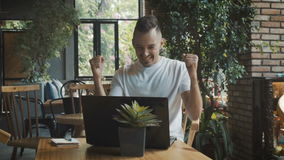 Business success - happy executive with laptop computer celebrating success achievement. Man working in cafe stock video footage