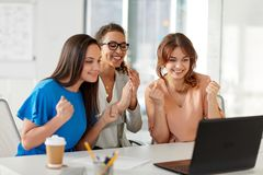 Happy businesswomen with laptop at office. Business, success and people concept - happy female team or businesswomen with laptop computer celebrating victory at Stock Photo