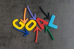 Business success strategy goals or new year resolution concept, colorful wooden alphabets GOAL at the center with pointing arrow. On black chalkboard cement stock photography