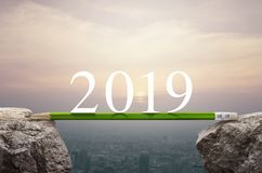 Business success strategy planning concept, Happy new year 2019. 2019 white text with green pencil on rock mountain over aerial view of cityscape at sunset stock image