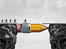 Business Success Symbol. And conquering adversity as a group of people running from one cliff to another with the help of a pencil acting as a bridge in a Royalty Free Stock Photos