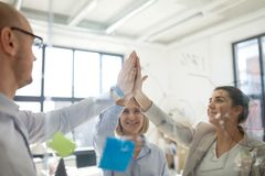 Close up of business team making high five stock photography