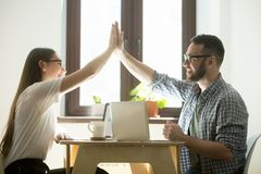 Business success: two happy employees making high five in office. Teamwork concept: businessman and businesswoman giving high five and congratulating each other Stock Photo