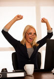 Business success - woman celebrating a victory or triumph behind. The desk in office after acheaving a great gol Royalty Free Stock Photography
