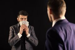 Business succsses. Man with beard on calm face sniffing money, smell of profit. Meeting of reputable businessmen, black. Background. Business payment concept royalty free stock image