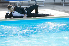 Business suit concept. Man sitting by the pool, wearing black suit feeling sad and dissapointed Stock Image