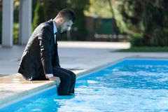 Business suit concept. Man sitting by the pool, wearing black suit feeling sad and dissapointed Royalty Free Stock Photos