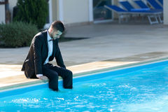 Business suit concept. Man sitting by the pool, wearing black suit feeling sad and dissapointed Stock Photos