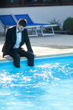 Business suit concept. Man sitting by the pool, wearing black suit feeling sad and dissapointed Royalty Free Stock Photography