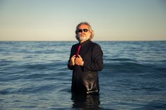 A business suit man posing in the sea. A man in a black suit poses looking at camera in the sea royalty free stock photos