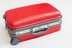 Business suitcase, red color on bed Stock Photos