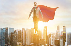 Business super hero hover over city skyline. Business superhero. Businessman in sketch super hero suit hovering over down town on sunset Royalty Free Stock Photos