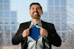 Business Super Hero. Mature Hispanic businessman opening shirt with office building in background Stock Image