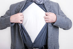 Business superman. A business man tears open his shirt in a super hero fashion getting ready to save the day Royalty Free Stock Photography
