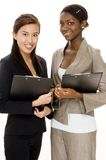 Business Survey. Two attractive young business women with clipboards Stock Photography