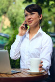 Business talk. Young woman talking on the phone in a cafe Royalty Free Stock Photo