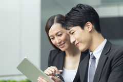 Business talk. Asian business women and men talk a pad and talk Royalty Free Stock Photo