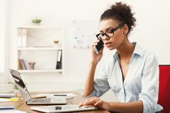 Business talk, serious woman talking on phone at office stock photography