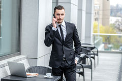 Business talk. A Serious young man in formal wear holding a phon Royalty Free Stock Images