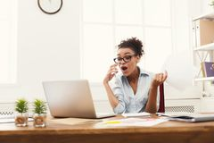 Business talk, surprised woman consulting by phone at office. Young surprised african-american businesswoman talking by phone with papers, sitting at modern Stock Photography