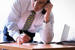 Business tasks. Closeup of a businessman talking on telephone and writing a note Stock Photos