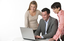 Business Team. A team of two females and one male working together at a computer. They are smiling. Horizontally framed shot Royalty Free Stock Photo