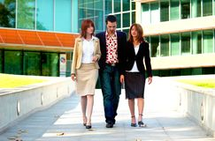 Business Team. A team of three co-workers walk away from the office as they discuss work Royalty Free Stock Images