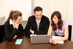 Business Team. One man and two women sitting in front of a laptop royalty free stock photography