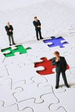 Business team. Figurine of a business men with their own different colored puzzle pieces maybe a team or not Royalty Free Stock Photos