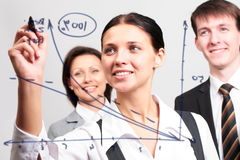 Business team. Business women drawing a graph on a glass window in an office Royalty Free Stock Image